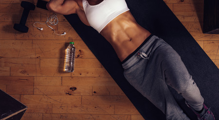 Top view of young woman with muscular abs lying on yoga mat in gym. Cropped shot of fitness woman relaxing after exercise session with a water bottle on floor, focus on stomach.