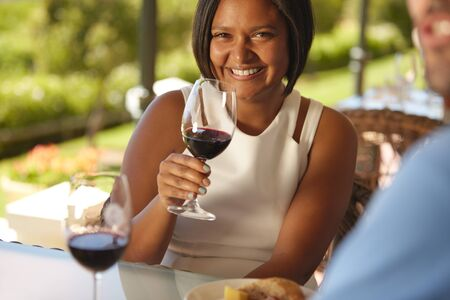 wine glasses: Portrait of beautiful young woman sitting at a table in winery holding a glass of red wine and smiling at camera. Stock Photo
