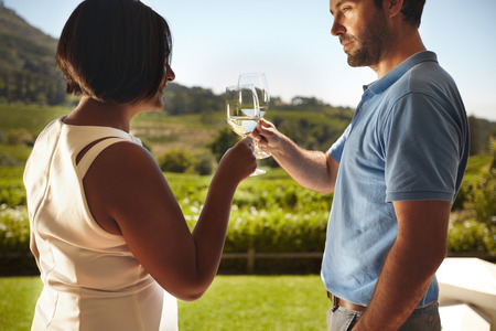 toasting wine: Closeup shot of young couple toasting wine while standing outdoors at winery restaurant with vineyard in background. Man and woman celebrating with wine on vacation .