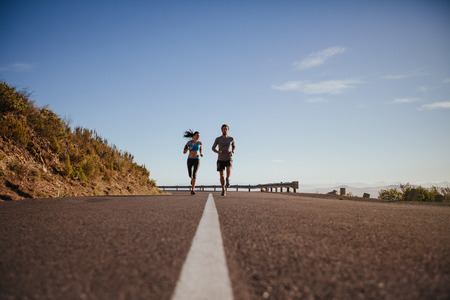 hacer footing: Ángulo de visión baja de dos jóvenes que se ejecutan en la carretera. Pareja joven trotar juntos en la carretera nacional en el día de verano con una gran cantidad de espacio de copia.