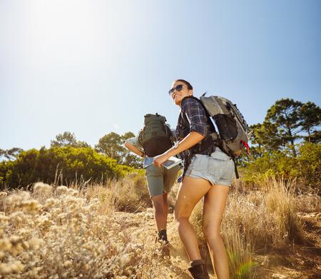 parejas: Los j�venes haciendo un camino cuesta arriba durante una excursi�n en el campo. Mujer con la correspondencia mirando hacia atr�s sobre el hombro sonriendo con el hombre que camina delante. Pareja en viaje de senderismo. Foto de archivo
