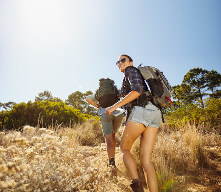 trip over: Young people doing a uphill climb while hiking in countryside. Woman with map looking back over her shoulder smiling with man walking in front. Couple on hiking trip.