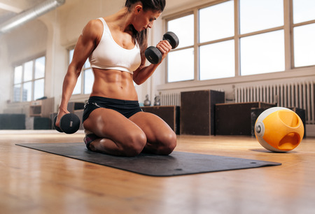 lifting hands: Physically fit woman at the gym lifting dumbbells to strengthen her arms and biceps. Muscular woman sitting on exercise mat looking at her arms. Stock Photo