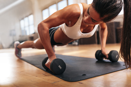 one female: Gym woman doing push-up exercise with dumbbell. Strong female doing crossfit workout.
