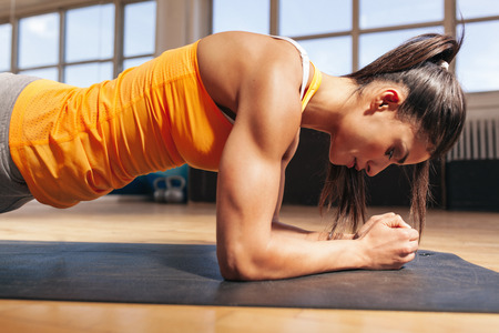 female pose: Side view of attractive young woman doing core exercise on fitness mat in the gym. Female doing press-ups in health club. Stock Photo