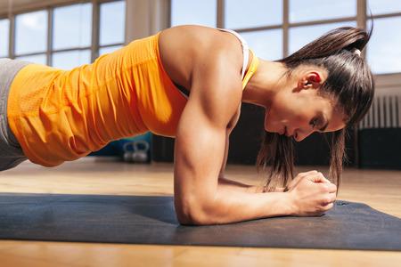 Vista laterale di giovane donna che fa esercitazione di base sul tappeto di fitness in palestra. Femmina che fa le flessioni in palestra.