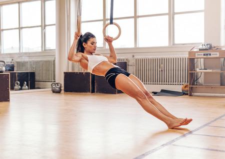 gymnastik: Junge Frau fit machen Klimmzüge an den gymnastischen Ringen. Muskulöse junge Sportlerin Ausübung mit Ringen auf Fitnessstudio.