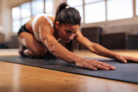focus on: Woman doing stretching workout on fitness mat, focus on hands, fitness female performing yoga on exercise mat at gym. Stock Photo