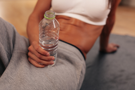 thirst: Close-up portrait of fitness woman holding water bottle at gym. Taking a break after training. Stock Photo