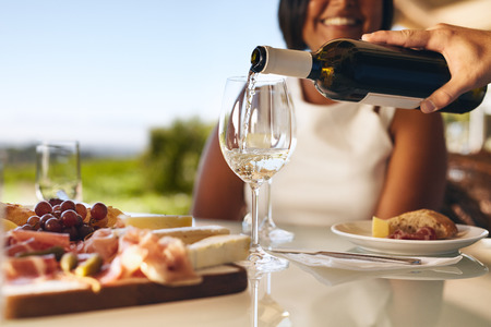 Hands of a man pouring white wine in two glasses from bottle with a woman smiling in background at winery. Focus on glasses and wine bottle.