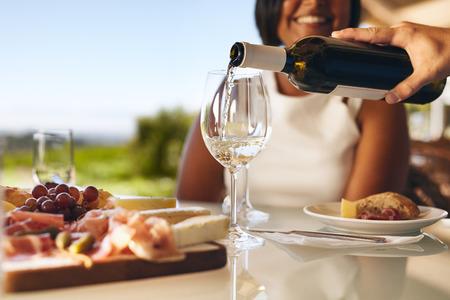Handen van een man gieten witte wijn in twee glazen uit de fles met een vrouw lachend op de achtergrond bij wijnmakerij. Focus op glazen en wijn fles.