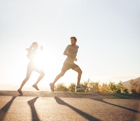 hacer footing: Los jóvenes que se ejecutan en la carretera nacional con la luz del sol brillante. Tiro al aire libre del hombre joven y una mujer corriendo en la mañana.