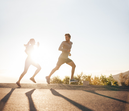 Young people running on country road with bright sunlight. Outdoor shot of young man and woman jogging in morning.