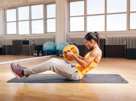 ejercicio: Vista lateral tirado de mujer joven muscular que hace entrenamiento crossfit usando pesas rusas. Modelo de la aptitud ejercicio en el gimnasio.
