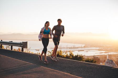 若いカップルが朝のジョギングします。若い男と女の山腹道に屋外を実行します。