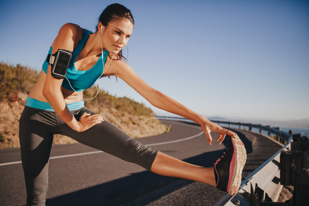 woman stretching: Determined young woman warming up before a run. Female athlete stretching her leg on road guardrail in morning. Stock Photo
