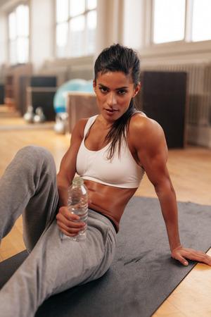 tomando refresco: Joven mujer sentada en una botella de agua celebraci�n estera de gimnasio. Aptitud femenina relajante despu�s de hacer ejercicio.