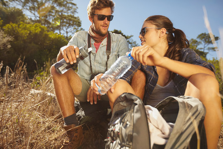 man drinking water: Young couple taking a break on a hike. Caucasian man and woman drinking water while out hiking