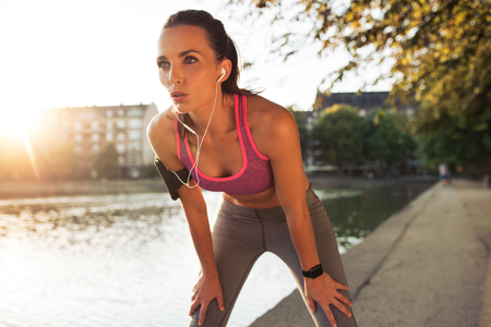 corriendo: Corredor femenino de pie se inclinó y recuperar el aliento después de una sesión a lo largo del lago en la ciudad. Mujer deportiva joven que toma el descanso después de una carrera.
