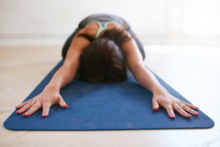 mat: Woman doing stretching exercise on yoga mat. Fitness female performing yoga on exercise mat at gym. Child Pose, Balasana.