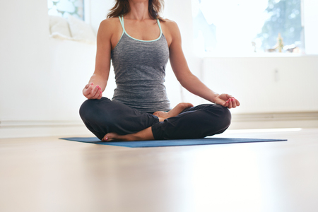 zen: Cropped shot of fit female sitting cross legged on exercise mat with hands on knees meditating. Woman in lotus pose at health club. Padmasana, meditation posture.