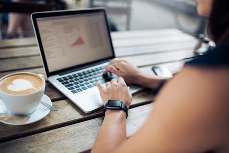 mecanografía: Recortar foto de una mujer en el café trabajando en su computadora portátil. Mujer SmartWatch lleva usando la computadora portátil con una taza de café en la mesa.
