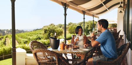 tomando vino: Pareja disfrutando de una copa de vino en un viñedo. Hombre joven y mujer que bebe el vino blanco mientras se está sentado en una mesa en una bodega.