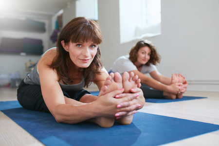 Women doing yoga together at gym, practicing paschimottanasana pose. Fitness female seated forward bend pose during training session.