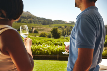 Couple standing together holding glasses of white wine with vineyard in background. Man and woman standing outdoors drinking wine at winery.