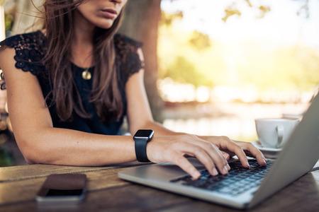 라이프 스타일: 랩톱 컴퓨터를 사용하여 스마트 워치를 착용하는 젊은 여자. 여성 야외 카페에서 노트북에서 작동합니다. 스톡 콘텐츠