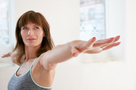 estiramientos: Retrato de la mujer de la aptitud que estira sus manos y mirando de lejos. Atractiva mujer madura que ejercita yoga en Virabhadrasana plantean. Mujer haciendo pose de Guerrero en el gimnasio.