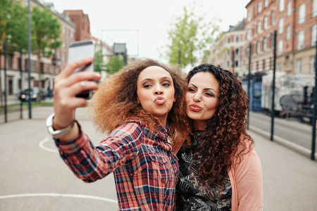 pout: Happy young girls pout and pose for a selfie. Young girl friends taking a self portrait using mobile phone, outdoors on city street. Stock Photo