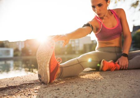 estiramientos: Corredor de la mujer joven que estira las piernas antes de hacer su entrenamiento de verano. La deportista calentamiento antes del entrenamiento al aire libre. Foto de archivo