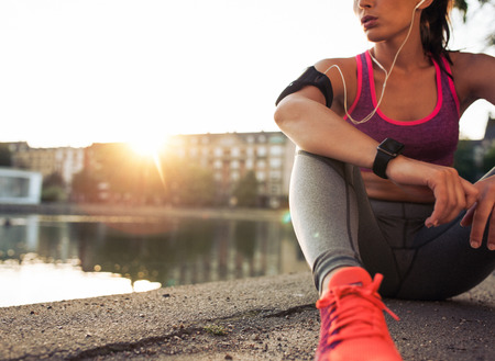 Young woman runner resting after workout session on sunny morning. Female fitness model sitting on street along pond in city. Female jogger taking a break from running workout.