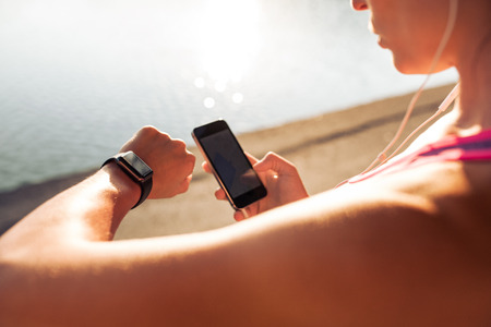 run: Sportswoman looking at smartwatch and holding smart phone in her other hand, outdoors. Fitness female setting up her smartwatch for her run. Stock Photo