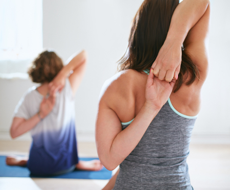 hands behind back: Rear view of women practicing gomukhasana in yoga class. Fitness females holding hands behind their back and stretching. Triceps and shoulders exercise. Stock Photo