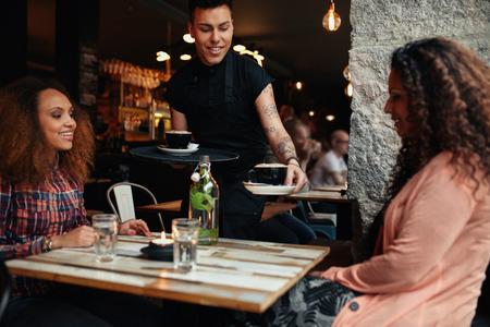 ウェイター レストランで若い女性にコーヒーを提供します。コーヒー ショップで女友達を 2 つ。