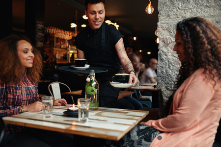 meseros: Camarero sirviendo caf� a las mujeres j�venes en el restaurante. Dos amigos femeninos en la cafeter�a.
