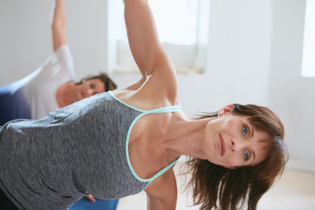 chandrasana: Portrait of mature woman doing stretches in a gym. Fitness trainer with student in background doing Ardha Chandrasana. half Moon pose. Stock Photo