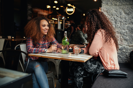2 people: Two young women talking sitting in a restaurant. African woman smiling and chatting with her friend in a cafe. Stock Photo
