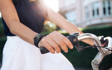 watch city: Woman riding a bike with a smartwatch. Female wearing smart watch while cycling. Smart watch concept. Stock Photo