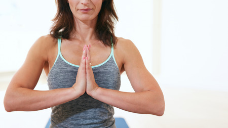 Cropped shot of fit woman practicing yoga in gym. Female fitness trainer sitting with her hands joined meditating. Anjali Mudra.