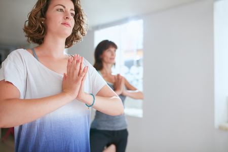 vriksasana: Portrait of young woman with her fitness trainer in background doing yoga exercising. Performing tree pose with hands clasped. Vrikshasana with namaste gesture.