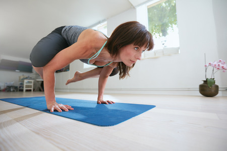 hands lifted up: Mature fitness woman standing on hands with feet lifted up doing crane yoga pose - Bakasana. Woman doing hands stand on exercise looking away.