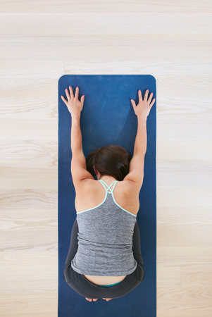 view woman: Top view of woman curls up and stretches forward, performing a yoga. Fitness female on exercise mat over light hardwood floors at health club. Woman practicing yoga at gym. Balasana pose. Stock Photo