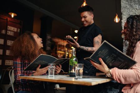 camarero: Alegres dos mujeres jóvenes sentados en el café que sostiene la tarjeta de menú dándole fin de camarero. Mujer joven de poner orden a un camarero en el restaurante mientras estaba sentado con su amiga.