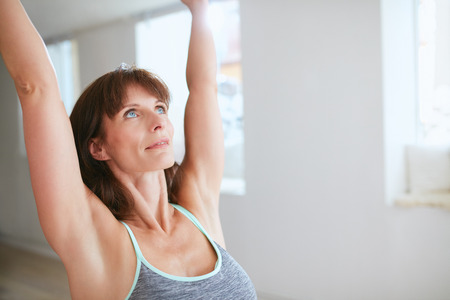 stretch: Close up shot of mature woman practicing yoga with her arms raised and looking upwards at gym. Fitness female in warrior pose I at yoga class.