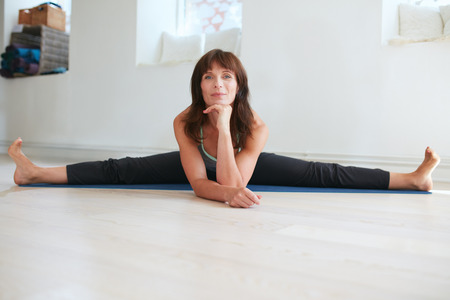 bending forward: Fitness woman doing wide angle seated forward bend yoga workout at gym. Upavistha Konasana exercise. Caucasian woman doing the splits.
