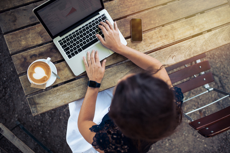 à  à     à  à    à  à female: Vista superior de la hembra usa su computadora portátil en un café. Tiro de arriba de mujer joven sentada en una mesa con una taza de café y el teléfono móvil navegando por la red en su ordenador portátil.
