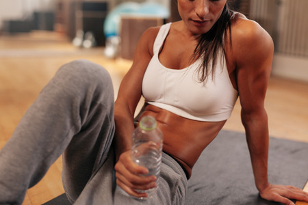 'fit body': Cropped shot of fitness woman holding water bottle at gym. Focus on water bottle. Female sitting on exercise mat.